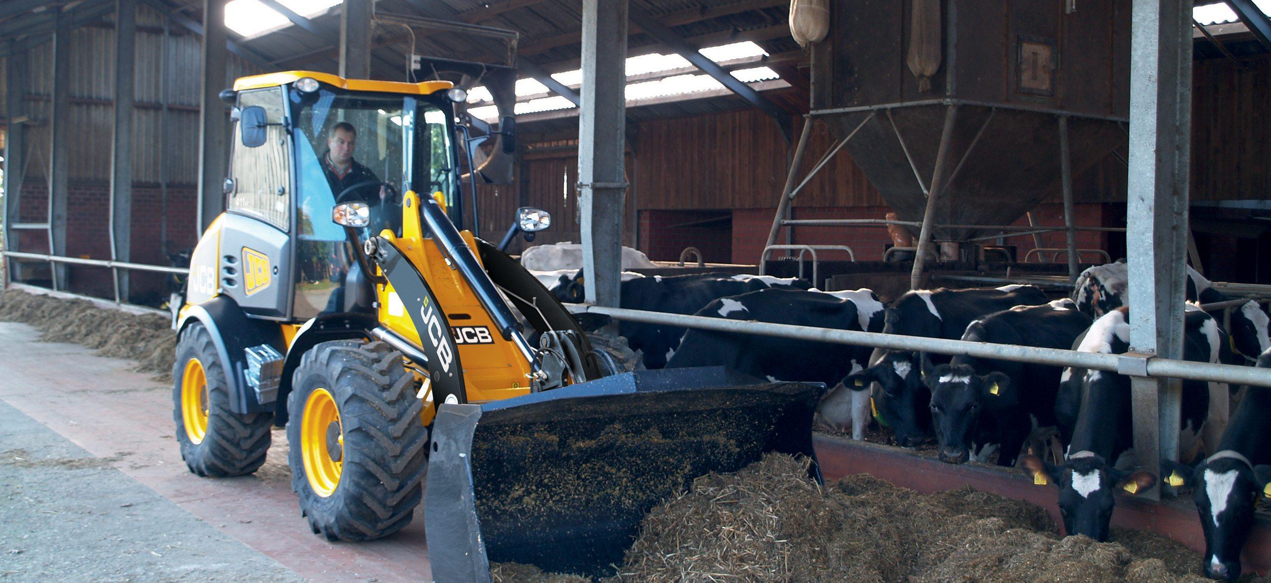 Landwirt bei der Stallreinigung im Kuhstall mit dem allradbetriebenen Hoflader.