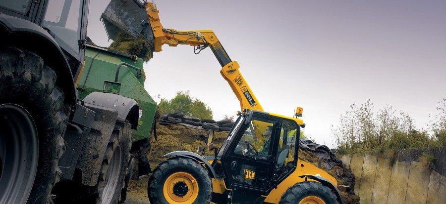 Landwirt lädt mit dem Kompakt Teleskoplader 525-60 Agri/Agri Plus Mist in einen Anhänger.