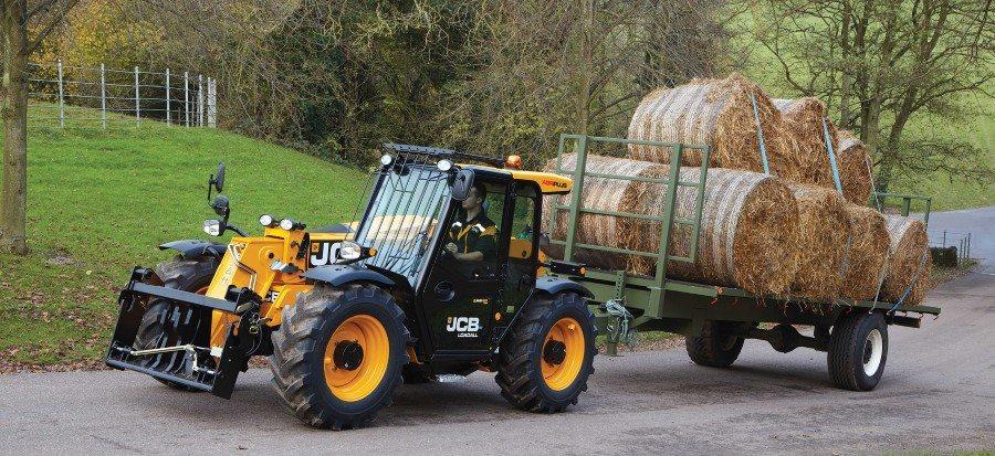 Landwirt transportiert fertig gewickelte Strohballen auf einem Anhänger mit dem Kompakt Teleskoplader 527-58-Agri.