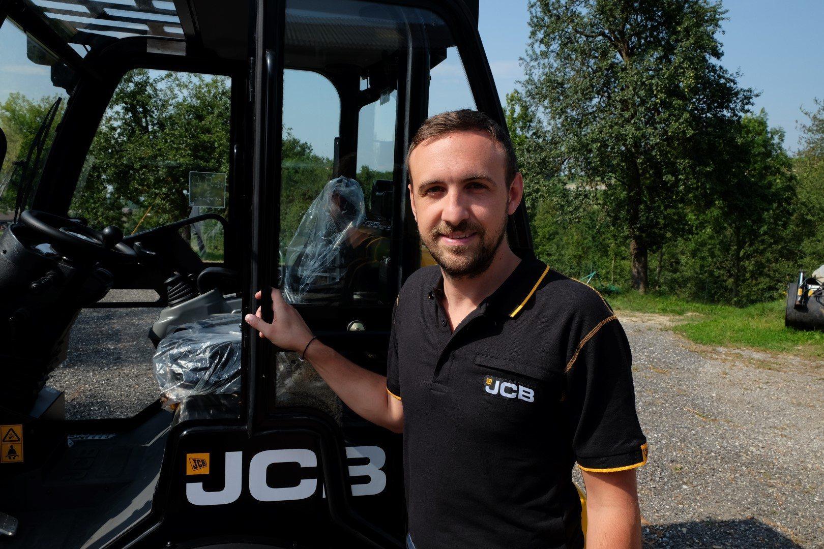 Produktexperte Dominik Babe mit steht neben einem Hoflader 403 Agri von JCB.
