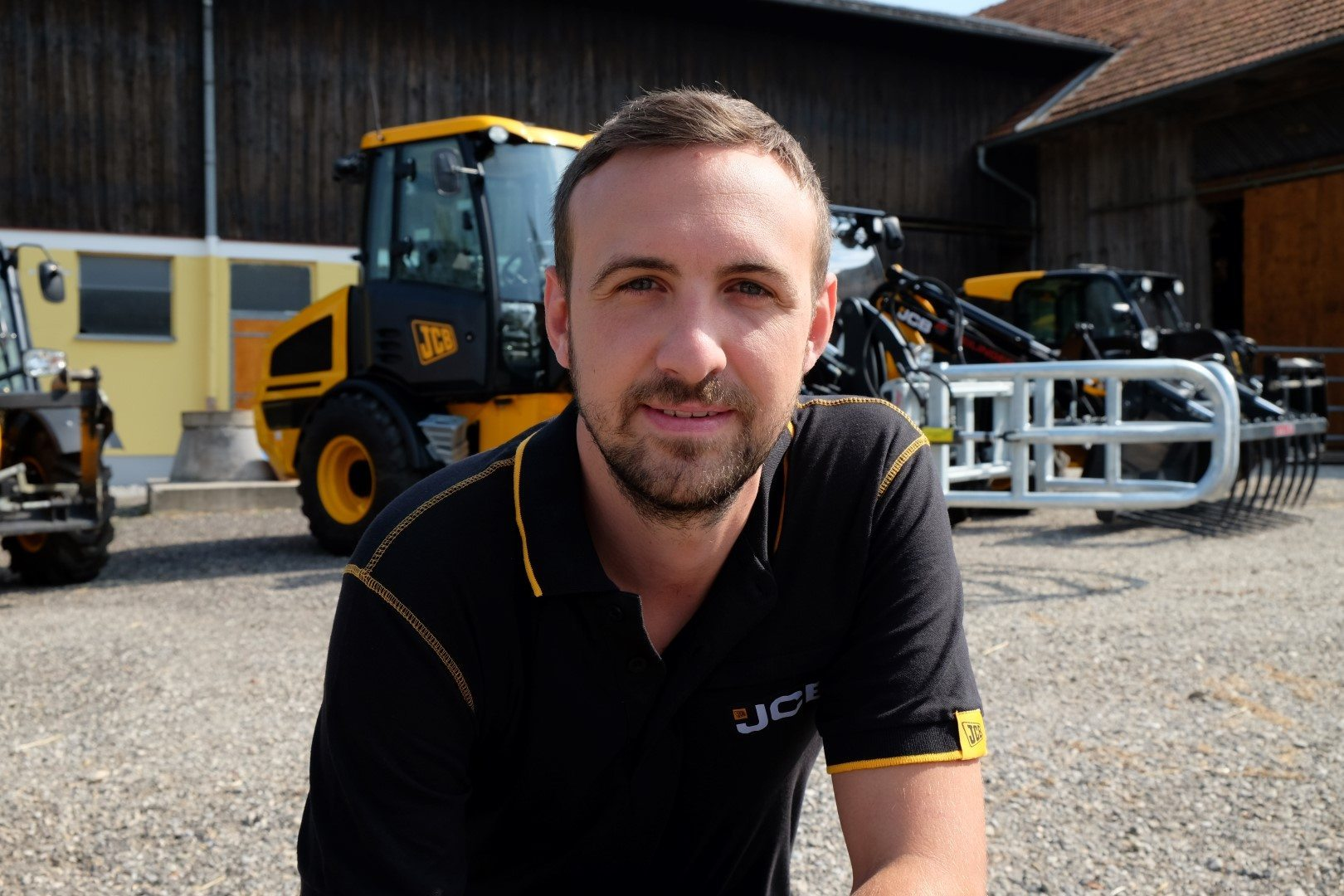Produktexperte Dominik Babe auf einem landwirtschaftlichen Hof, im Hintergrund Landtechnikmaschinen von JCB.
