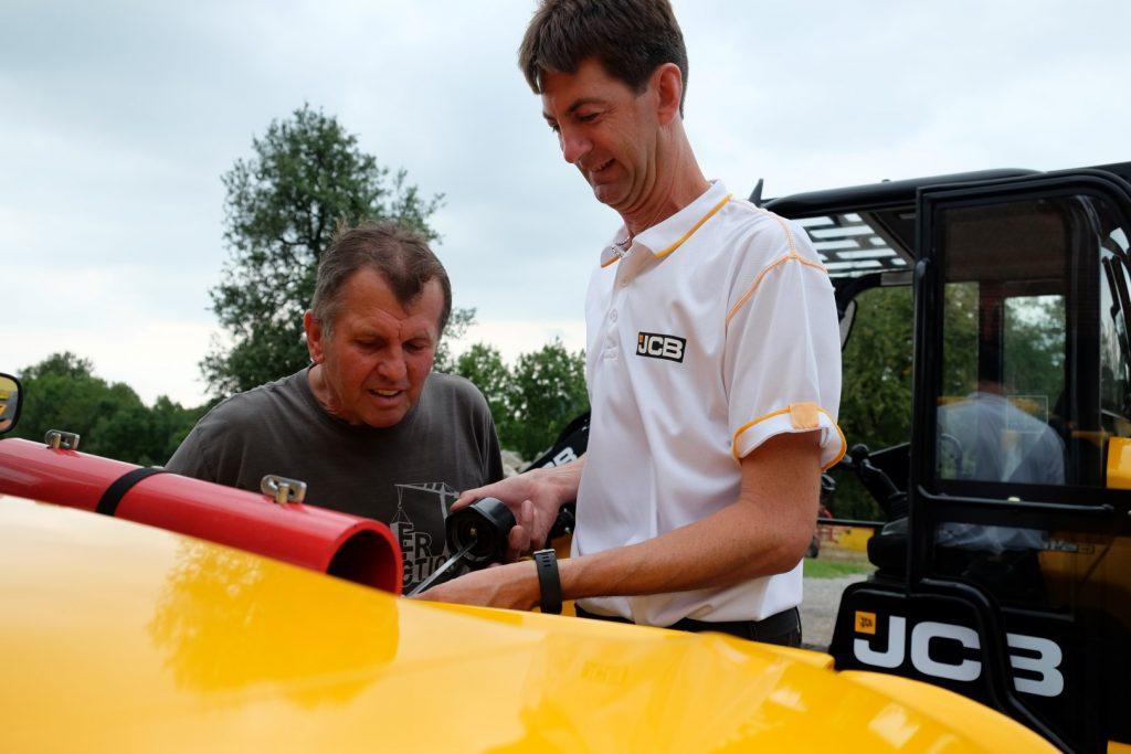 Servicetechniker mit einem Kunden beim Prüfen der Flüssigkeitsstände.