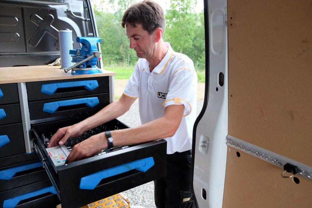 Servicetechniker sucht passendes Werkzeug in der Werkzeugkiste im Servicebus.