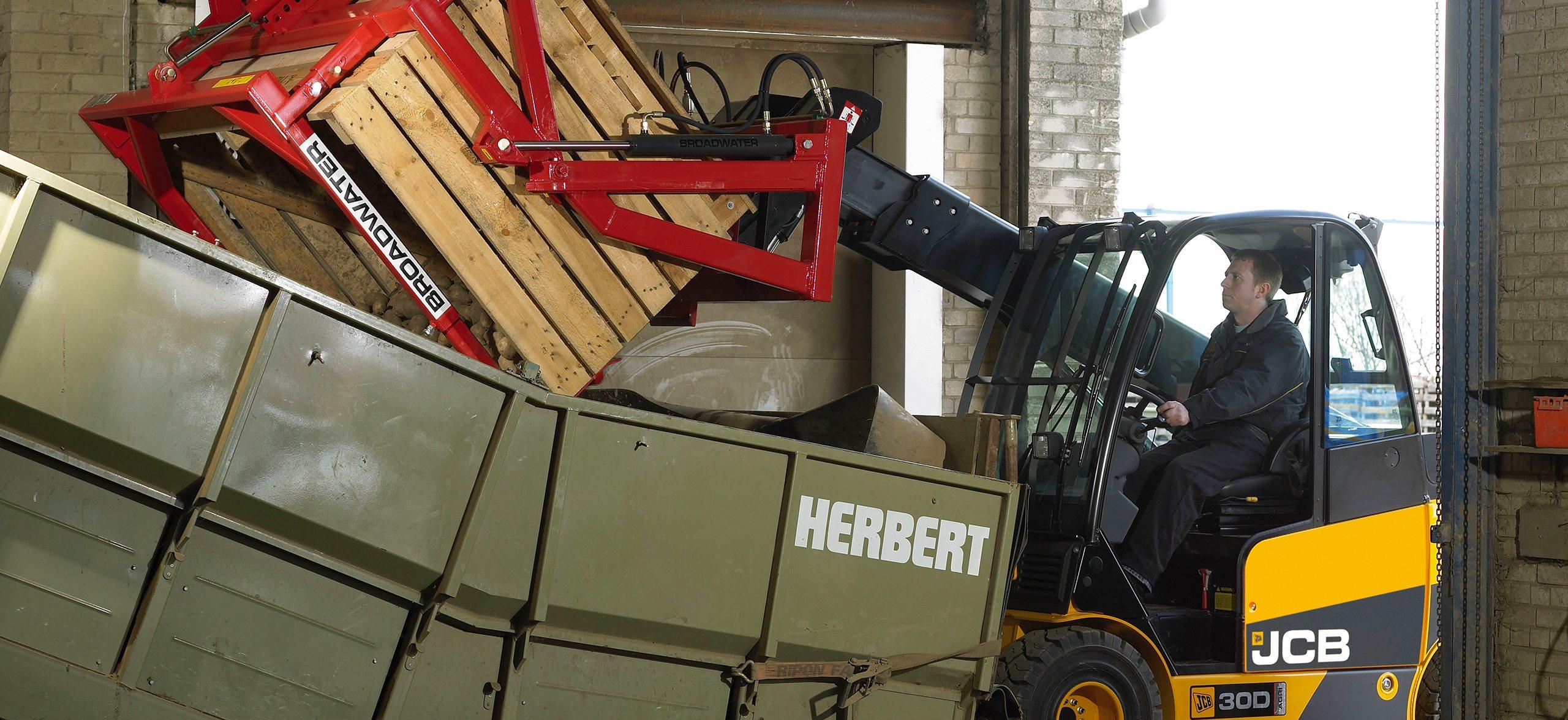 Landwirt leert mit dem JCB Teletruk den Inhalt einer Kiste in einen Container